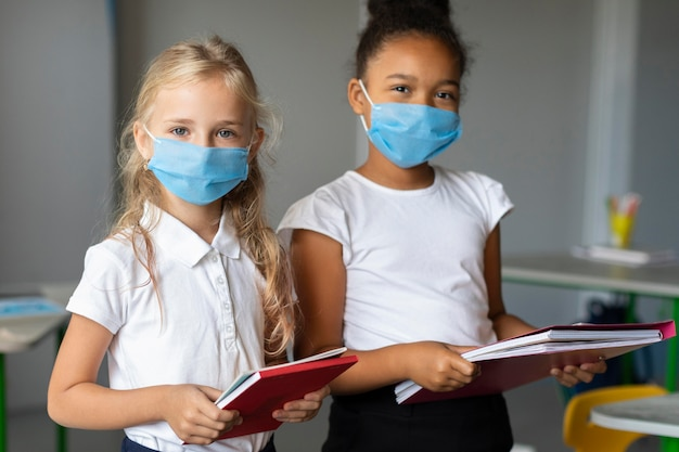 Niñas con máscaras médicas en clase.