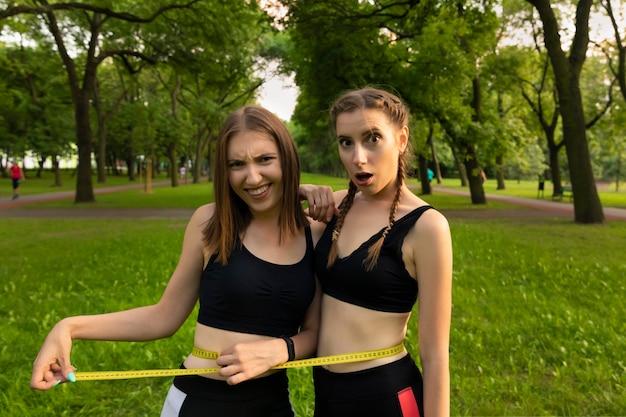 Niñas midiendo sus caderas en un parque