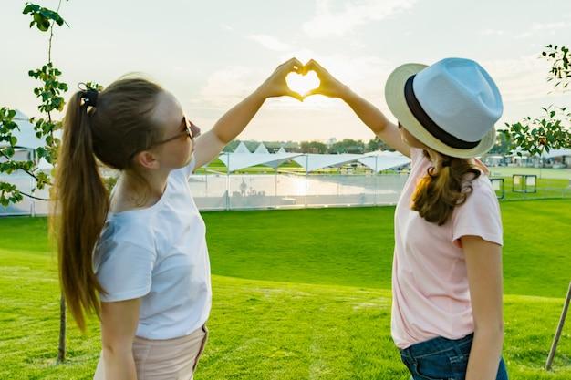 Las niñas muestran las manos en el corazón en el fondo del atardecer
