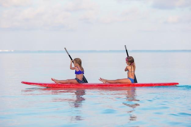 Niñas nadando en la tabla de surf durante las vacaciones de verano
