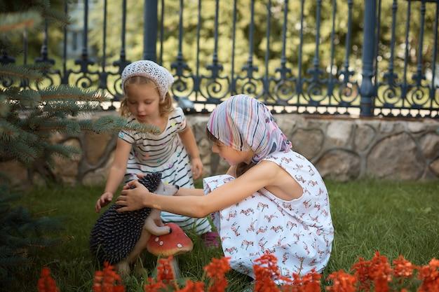 Niñas ortodoxas rusas consideran flores cerca de la iglesia