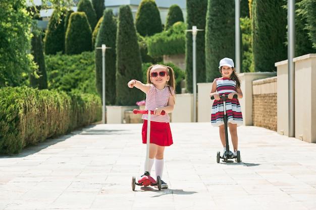 Niñas de preescolar montando scooter al aire libre.
