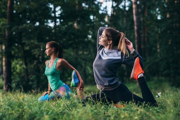 Las niñas sentadas en una pierna de la paloma real posan durante la sesión de entrenamiento en el campamento de yoga