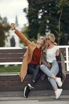 Las niñas sentadas en una primavera sity y sostienen el café en la mano