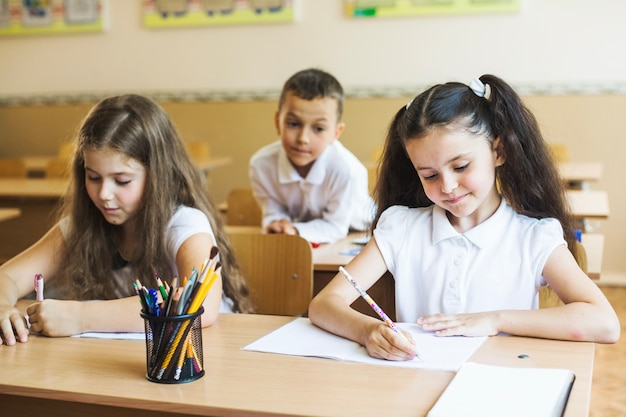 Niñas, sentado, escritorio, sala de clase, escritura