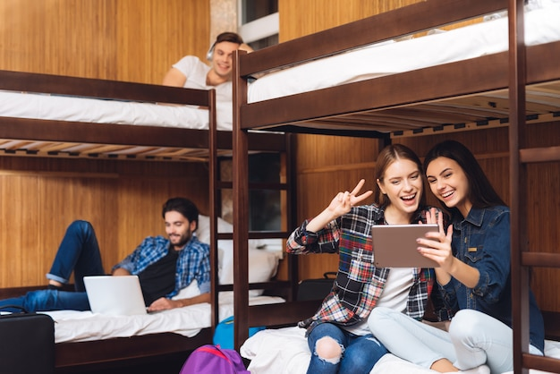 Las niñas se sientan en la cama y hablando en video en la tableta.