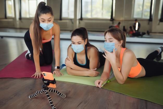 Las niñas siguen de cerca al maestro en línea a través de un teléfono inteligente. chicas con máscaras protectoras