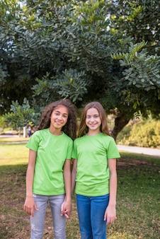 Niñas sonrientes de pie delante de un árbol en el parque