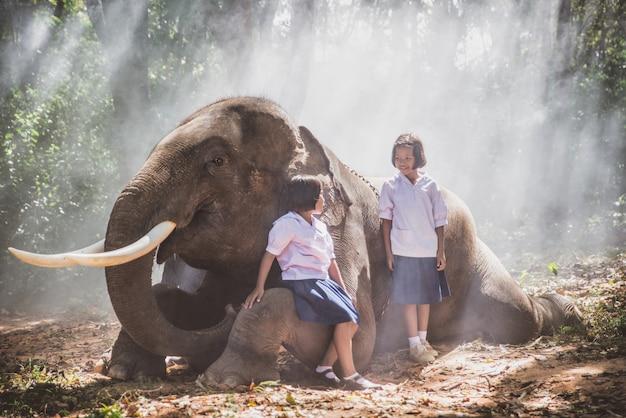 Niñas tailandesas jugando después de la escuela en la selva cerca de su amigo elefante