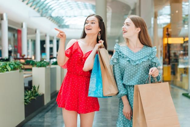 Niñas de tiro medio mirando lejos en el centro comercial