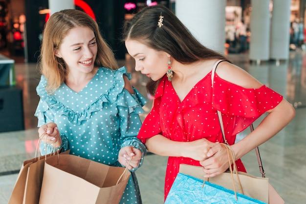 Niñas de tiro medio revisando sus bolsas de compras.