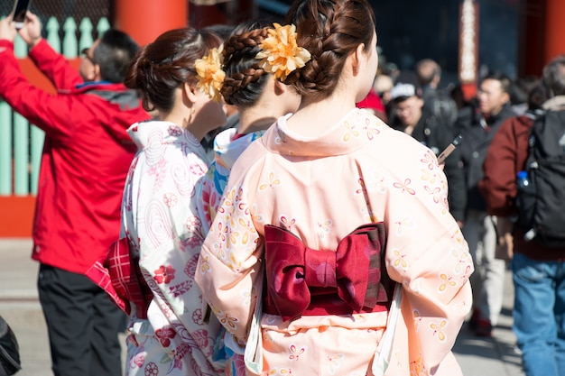 Las niñas usan yukata a pie en el templo de japón.