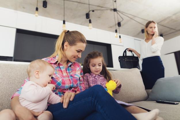 La niñera está jugando con la niña y el bebé en el sofá.