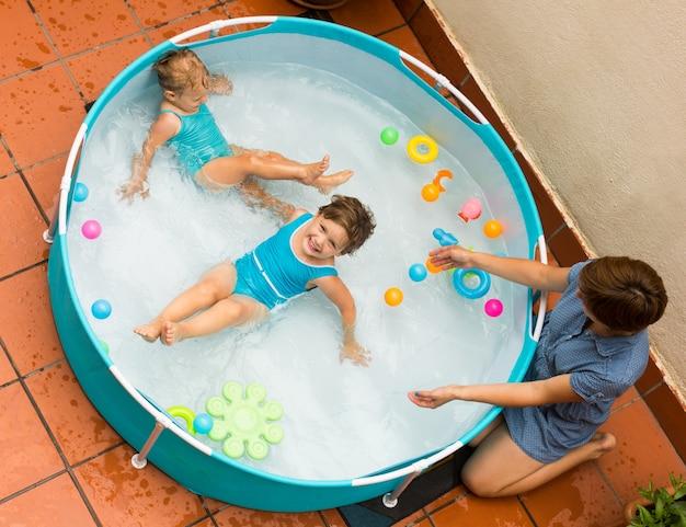 Niñera con niñas en la piscina