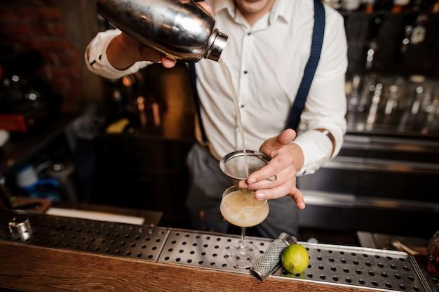 Ningún barman de la cara está vertiendo cóctel en el vaso en el soporte de la barra