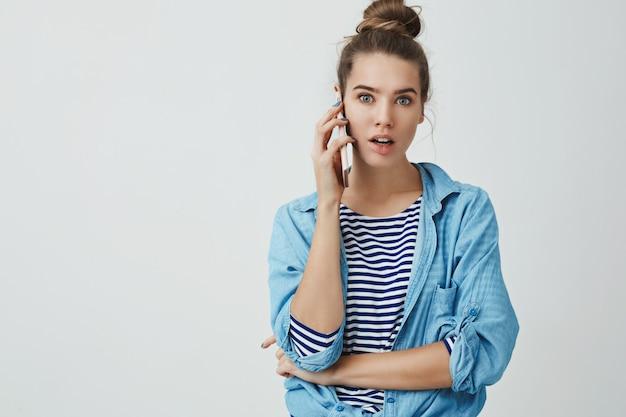 De ninguna manera, wow. impresionada, abrumada, guapa, jovencita cotilleando durante la conversación telefónica, ensancha los ojos, emocionada, atónita, escuchando chismes increíbles sosteniendo el teléfono inteligente presionando el oído