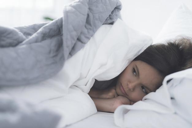 Una niñita negra yace en una cama blanca debajo de una manta blanca.