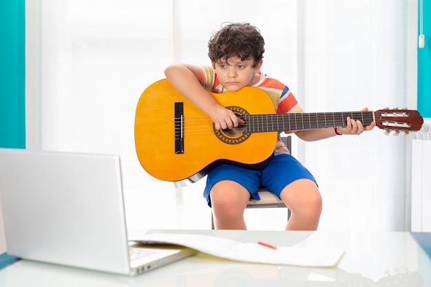 Niñito en casa tocando la guitarra española frente a su computadora portátil