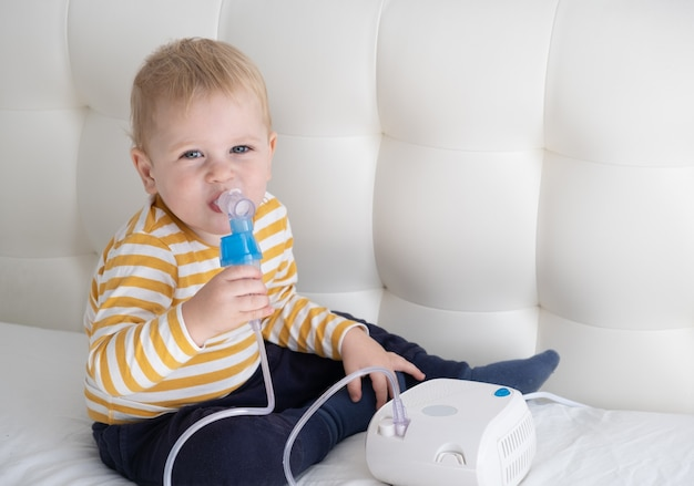 Niñito con inhalador de vapor nebulizador él mismo en la cama. atención médica de salud.