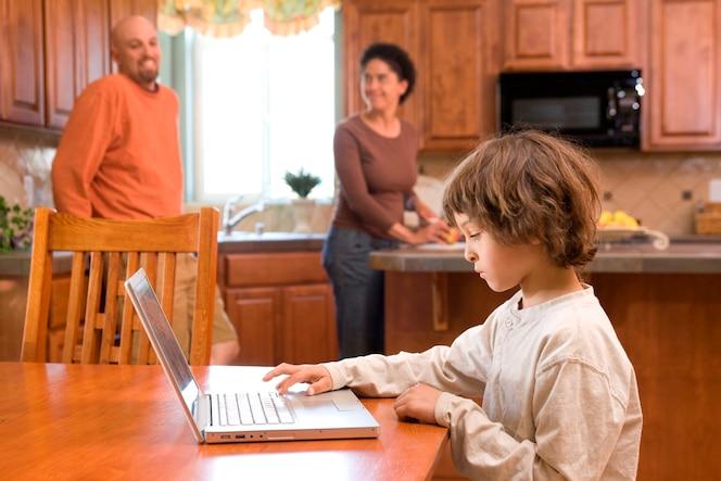 Niño (4-5) usando una computadora portátil mientras los padres están de pie en el fondo