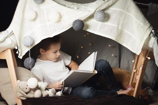 El niño de 7 a 11 años se sienta en una cabaña de sillas y mantas. niño, libro de lectura en casa