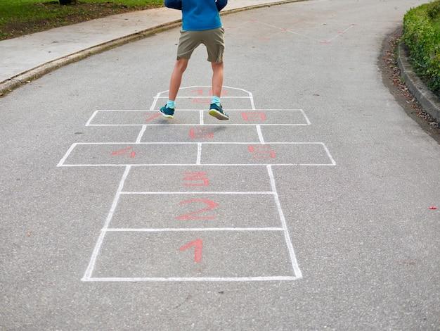 Niño de 8 años, juego, rayuela, vista trasera