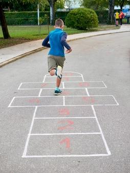 Niño de 8 años saltando y jugando a la rayuela, vista posterior