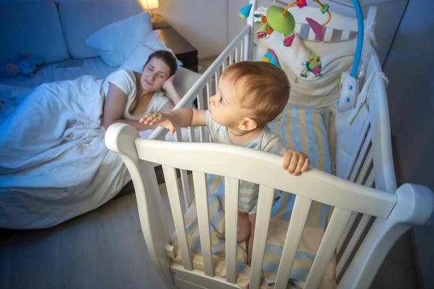 Niño de 9 meses de edad de pie en la cuna y despertando a su madre dormida