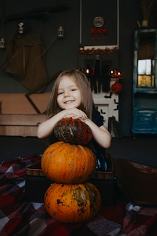 Un niño abraza un primer plano de calabaza en una fiesta de halloween.