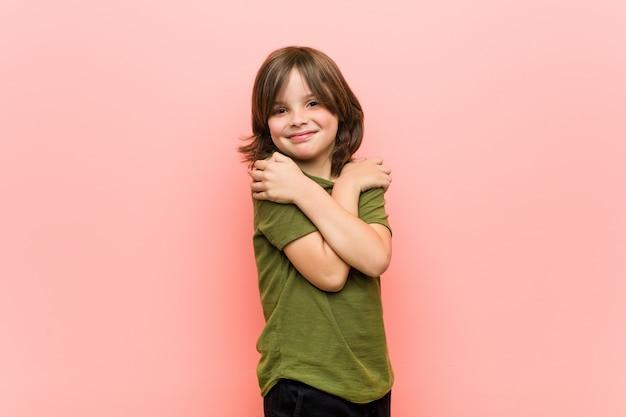 Niño abraza, sonriendo despreocupado y feliz.