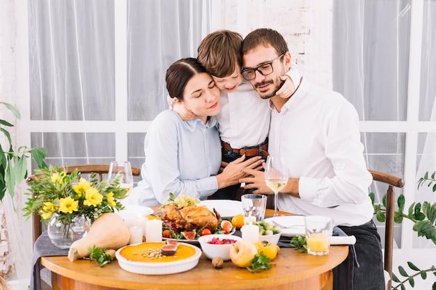 Niño abrazando a los padres en la mesa festiva