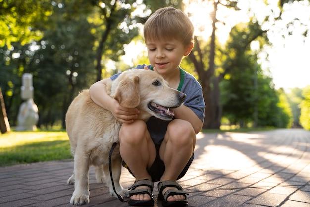 Niño abrazando a un perro de tiro completo en el parque