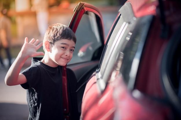 Niño abre la puerta del coche para entrar.