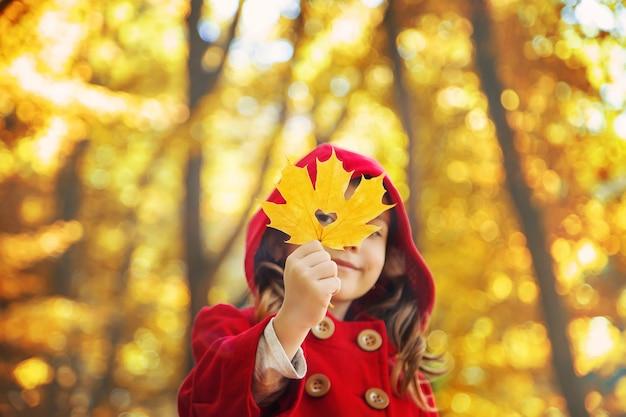 Niño en un abrigo rojo con hojas de otoño. me encanta el otoño enfoque selectivo