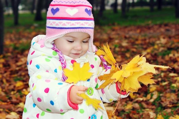 Niño en un abrigo rojo con hojas de otoño.