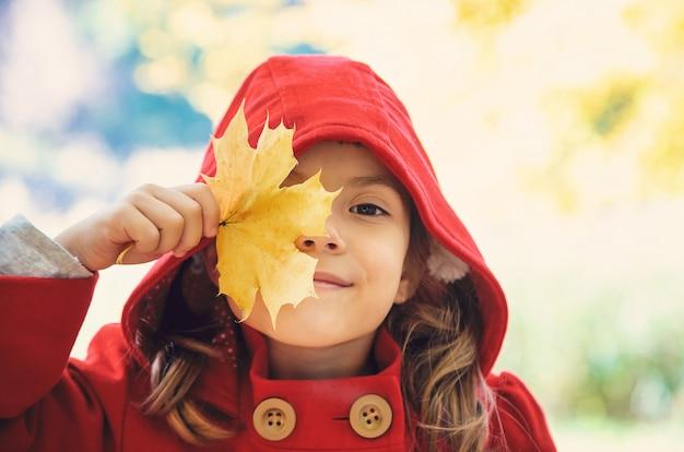 Niño en un abrigo rojo con hojas de otoño