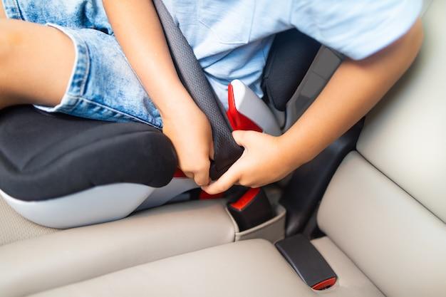 El niño se abrocha el cinturón de seguridad en el auto.