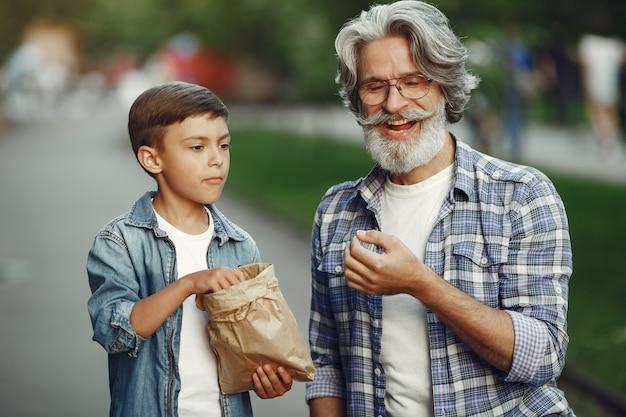 Niño y abuelo están caminando en el parque. anciano jugando con su nieto. la gente come palomitas de maíz.