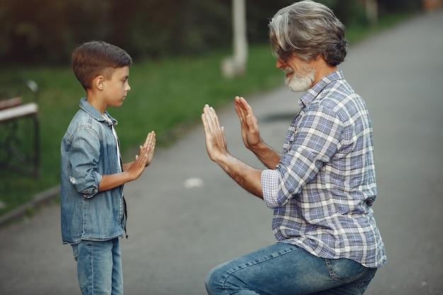 Niño y abuelo están caminando en el parque. anciano jugando con su nieto.