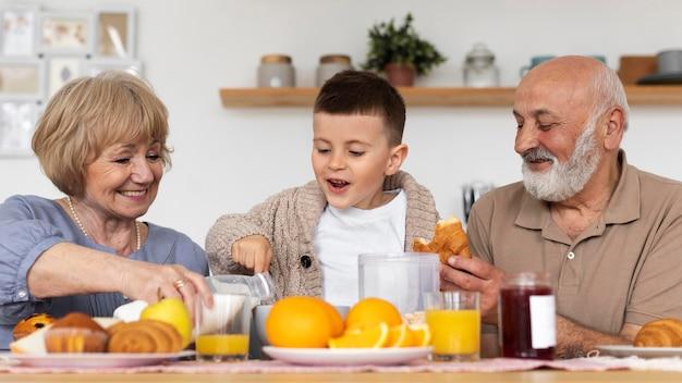 Niño y abuelos felices de tiro medio