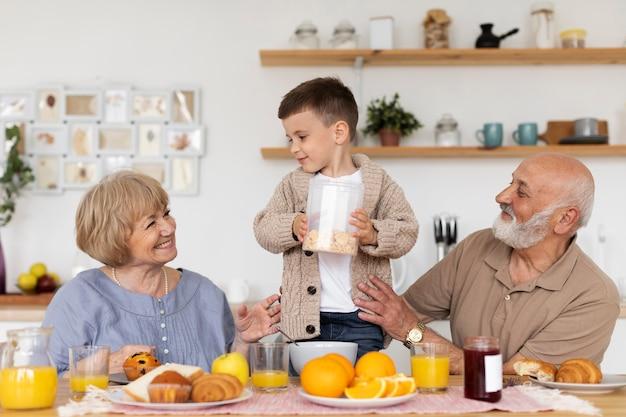 Niño y abuelos sonrientes de tiro medio
