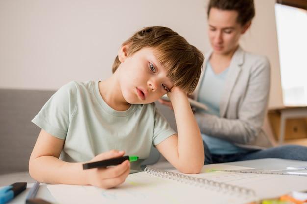 Niño aburrido en casa mientras recibe tutoría