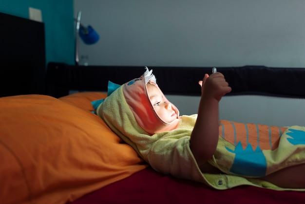 Niño acostado en la cama en una bata de baño viendo videos de tableta