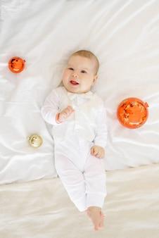 El niño está acostado en la cama en el dormitorio rodeado de bolas de juguetes de árbol de navidad y riendo
