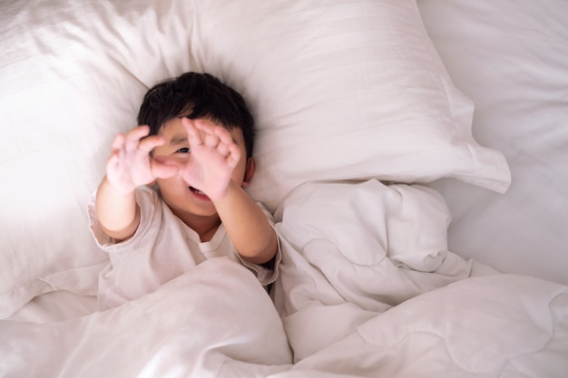 Niño acostado jugando y sonriendo en la cama blanca con almohada y manta