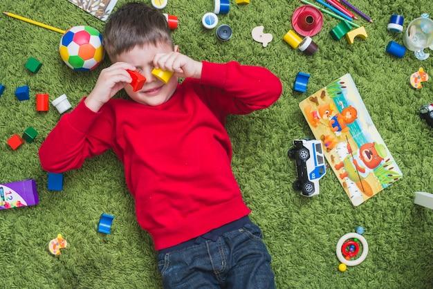 Niño acostado en un lío de juguetes