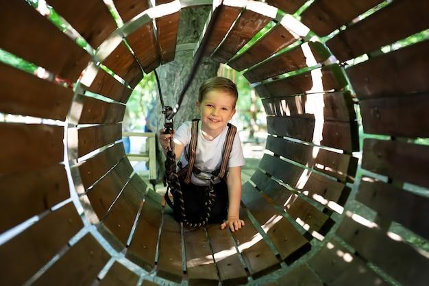 Niño activo que se sube a una cuerda en el camino hacia el parque de atracciones en el verano