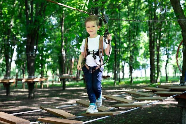 Niño activo que se sube a una cuerda el camino hacia el parque de atracciones.