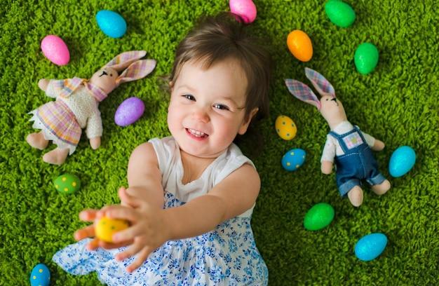 Niño se acuesta en la hierba con huevos de pascua y una liebre