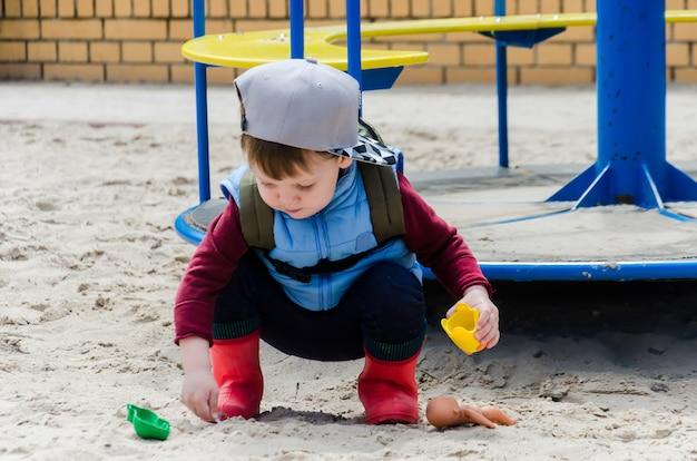 Niño se adentra en la arena cerca del carrusel infantil